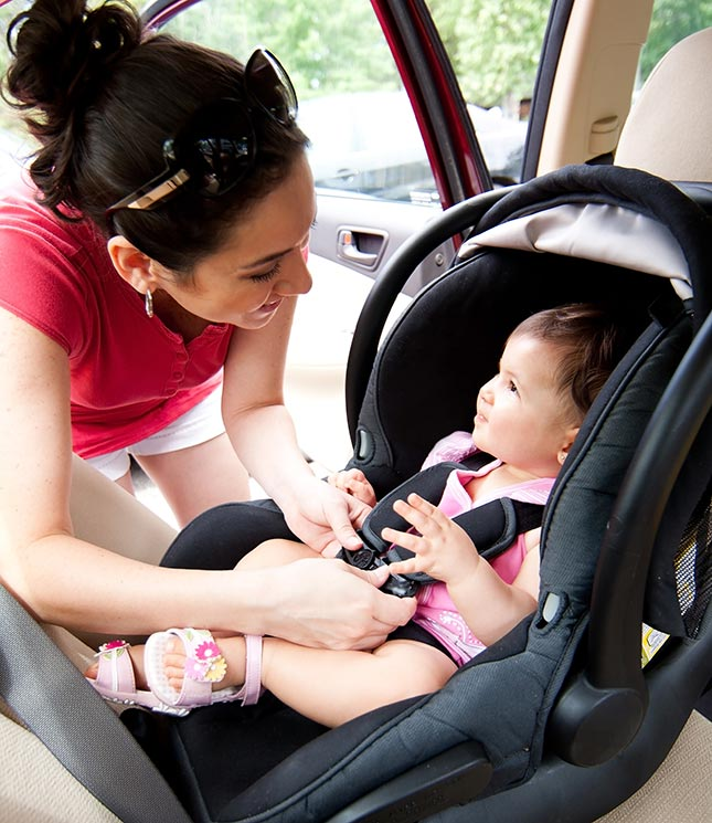 Woman putting baby in car seat